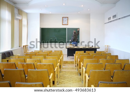 Teacher clears with blackboard in empty classroom, back view