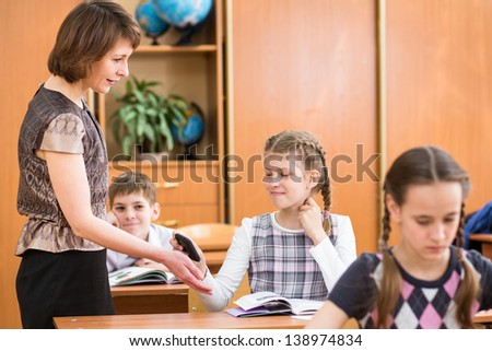 Teacher confiscating schoolkid's mobile phone at lesson - stock photo