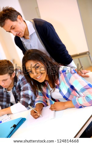 Teacher controlling group of students with paperwork - stock photo