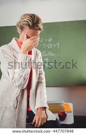Teacher crying in front of blackboard at school - stock photo