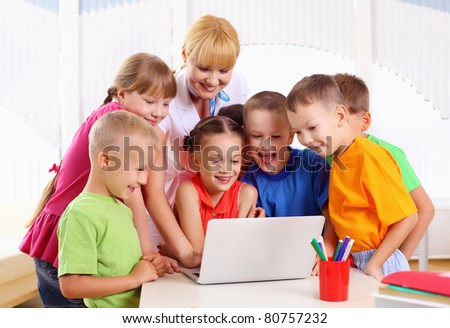 teacher deals with students for a laptop at school - stock photo