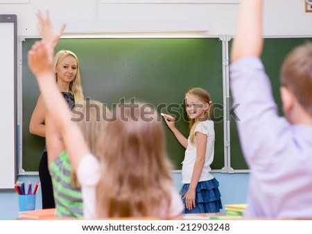 teacher during the lesson tests knowledge of students who raise their hands up - stock photo