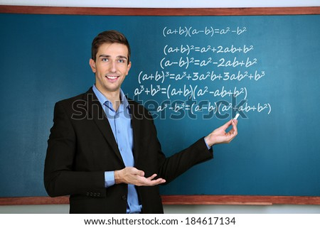 Teacher explaining formulas written on blackboard to  pupils - stock photo
