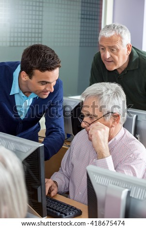 Teacher Explaining Senior Men In Computer Class - stock photo