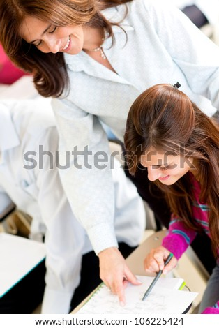 Teacher explaining something to a female student in class - stock photo