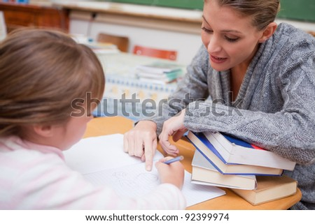 Teacher explaining something to her pupil in a classroom - stock photo