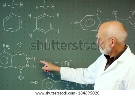 Teacher explains something in chemistry class - stock photo