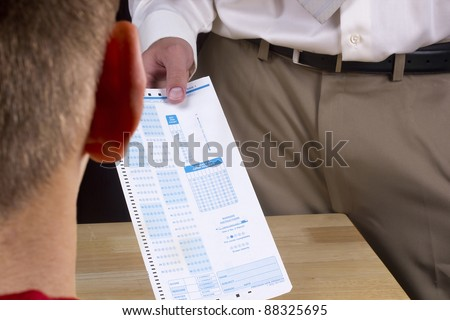 Teacher giving a multiple choice test to a student. - stock photo