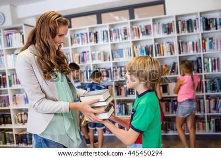 Teacher giving books to her students at school