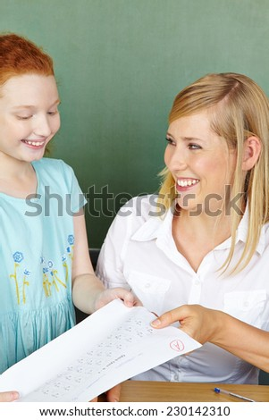 Teacher giving girl test back with a very good grade in elementary school - stock photo