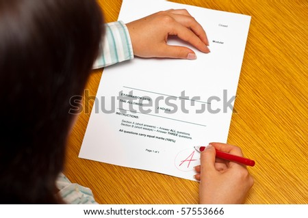 teacher grading an exam paper - stock photo