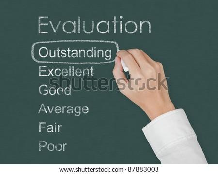 teacher hand evaluate outstanding on chalkboard - stock photo