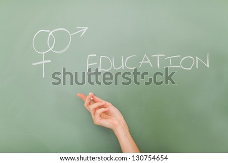 teacher hand pointing at sex education symbol written on the chalkboard