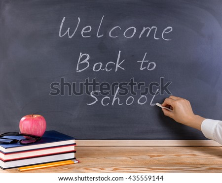 Teacher hand writing on erased black chalkboard. Desktop with books, apple, pencils, and reading glasses in forefront. Back to school concept.