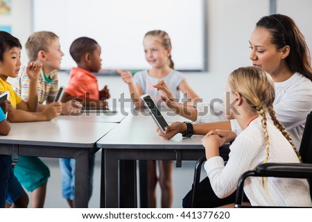 Teacher having lesson with tablet pc in classroom - stock photo