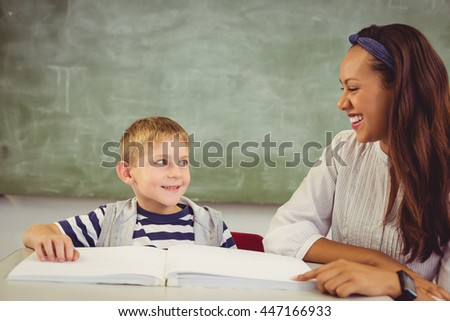 Teacher helping a boy with his homework in classroom at school