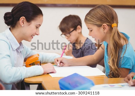 Teacher helping a little girl during class at the elementary school