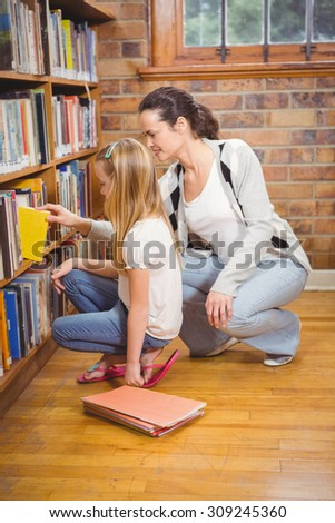 Teacher helping a student pick a book at the elementary school - stock photo