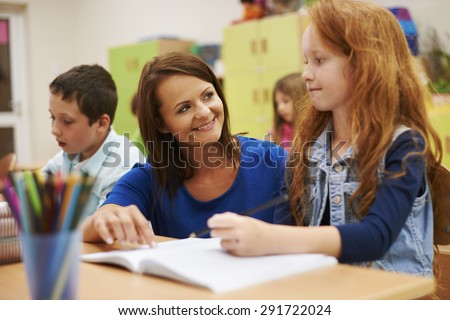 Teacher helping her cute pupil - stock photo