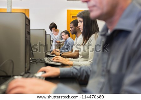Teacher helping her students in computer class in college - stock photo