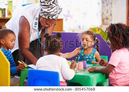 Teacher helping kids in a preschool class - stock photo