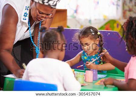 Teacher helping kids in a preschool class, close up - stock photo