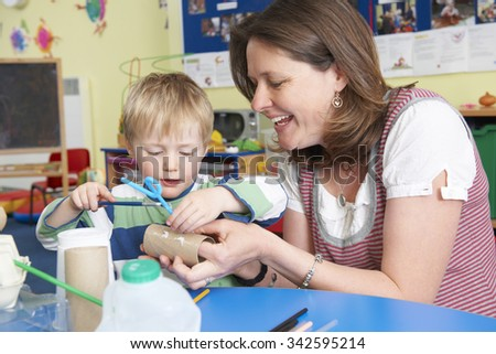 Teacher Helping Little Boy To Build Model In Art Class - stock photo