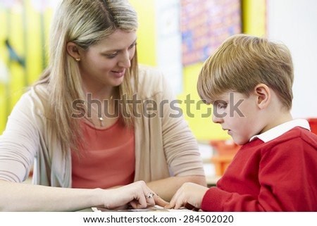 Teacher Helping Male Pupil With Reading At Desk - stock photo