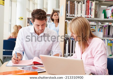 Teacher Helping Mature Student With Studies In Library - stock photo