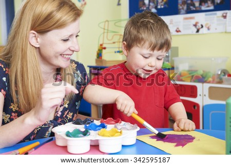 Teacher Helping Preschool Child In Art Class