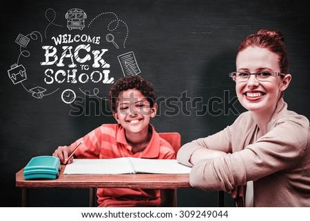 Teacher helping pupil against blackboard - stock photo