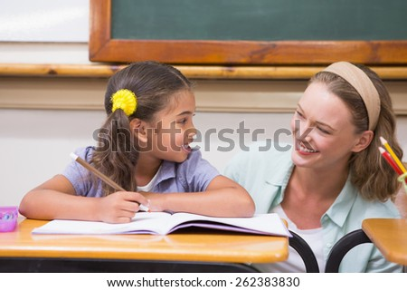 Teacher helping pupil in classroom at the elementary school - stock photo