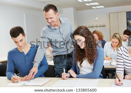 Teacher helping pupil in school class in a classroom - stock photo