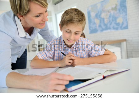 Teacher helping pupil with reading in class - stock photo