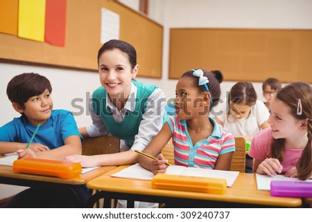Teacher helping pupils during class at the elementary school