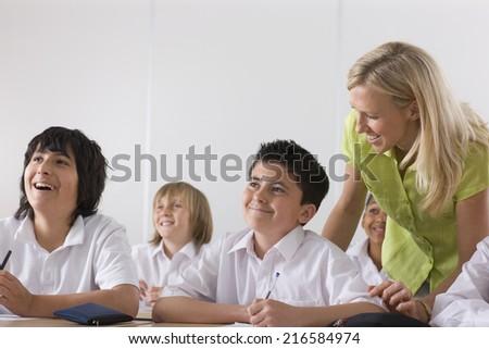 Teacher helping school boy in classroom - stock photo