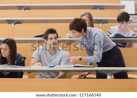 Teacher helping student at the lecture hall - stock photo