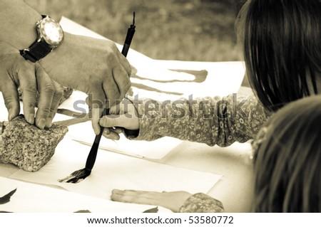 Teacher Helping Student drawing hieroglyph - stock photo