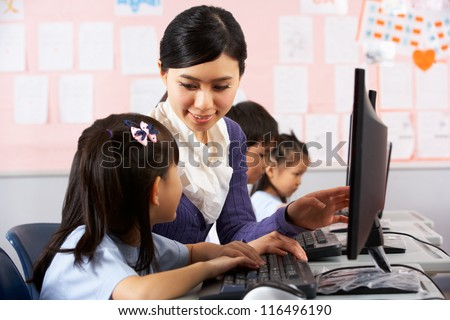 Teacher Helping Student During Computer Class In Chinese School Classroom