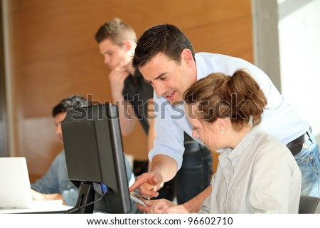 Teacher helping student girl with project - stock photo