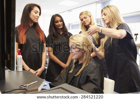 Teacher Helping Students Training To Become Hairdressers - stock photo