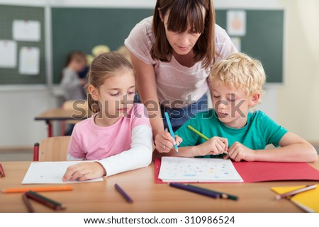 Teacher helping two small kids in the classroom as she leans over them to write something on the little boys work, both children watching with solemn faces