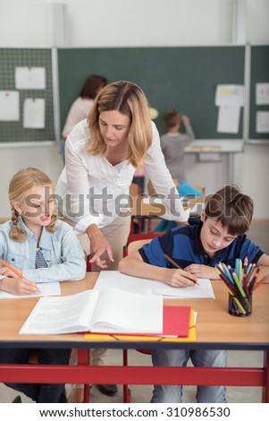 Teacher helping two young schoolchildren sitting at a desk together in the classroom leaning over from behind pointing to a textbook - stock photo