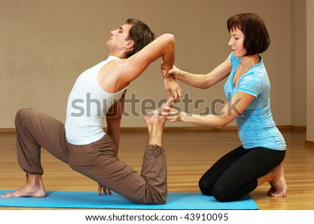 teacher helping with yoga pose indoors - stock photo
