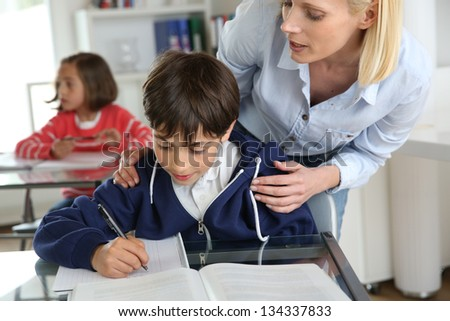 Teacher helping young boy with lesson