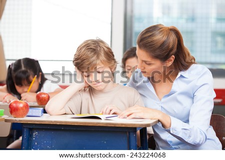 Teacher helping young boy with writing lesson in classroom. - stock photo