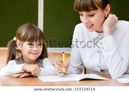 Teacher helping young girl with writing lesson - stock photo