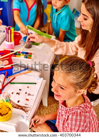 Teacher helps a group of children to draw.  Development of creative abilities of children. - stock photo