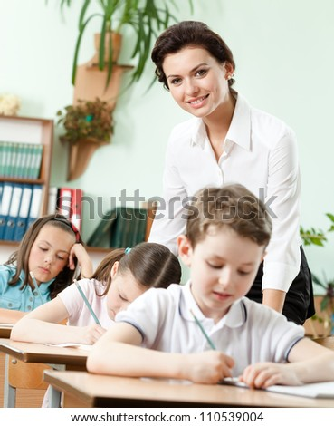 Teacher helps her pupils to do the task at school - stock photo