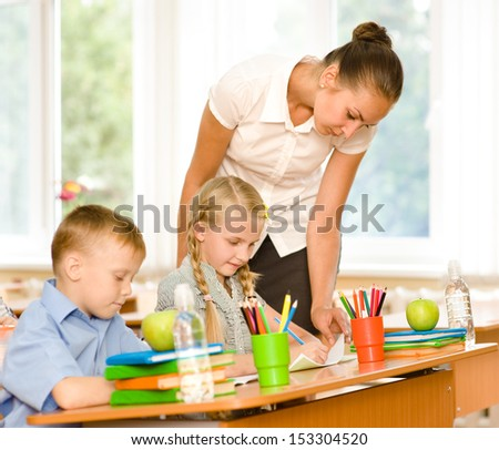 Teacher helps the schoolkids with schoolwork in classroom - stock photo
